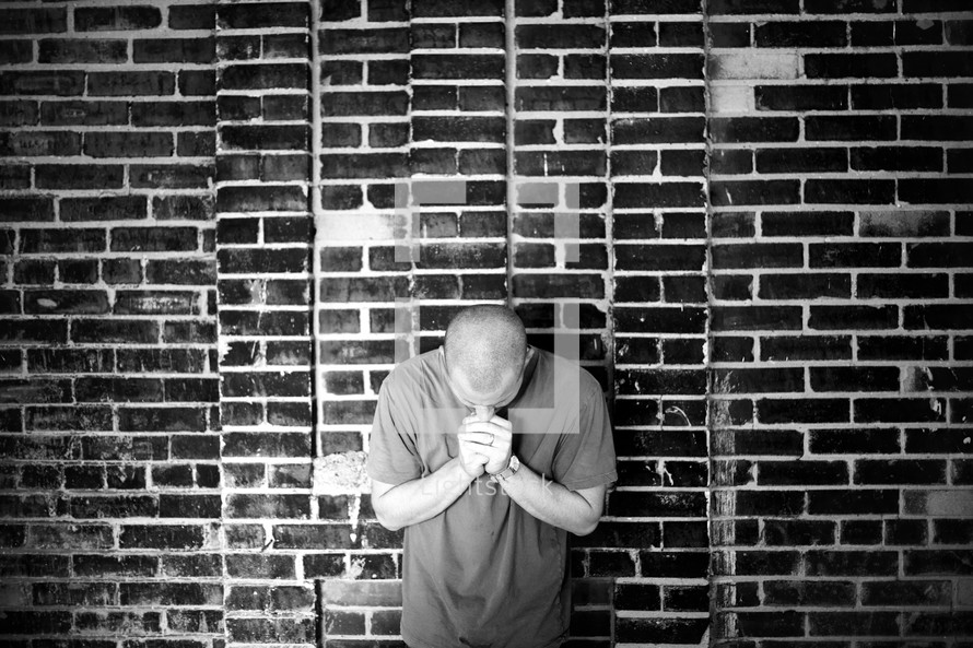 A man praying against a brick wall