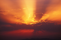 rays of sunlight from behind dark clouds give a brilliant red, orange, and yellow sky