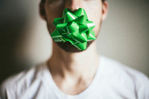 A man with a Christmas bow taped over his mouth