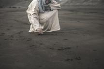 Jesus squatting on a beach