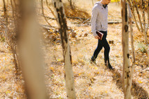 a man walking through a forest carrying a Bible