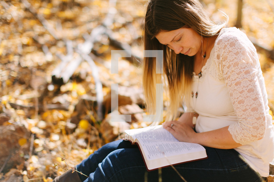 a woman sitting in fall leaves reading a Bible