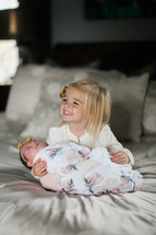 a big sister holding a baby on a bed
