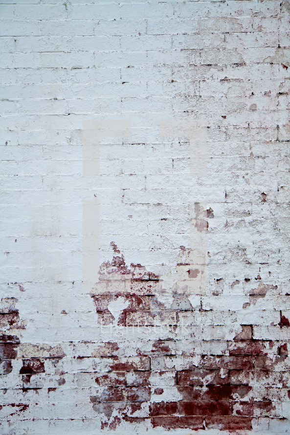 white paint peeling from a brick wall