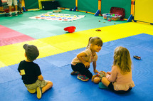children sitting on mats in childcare
