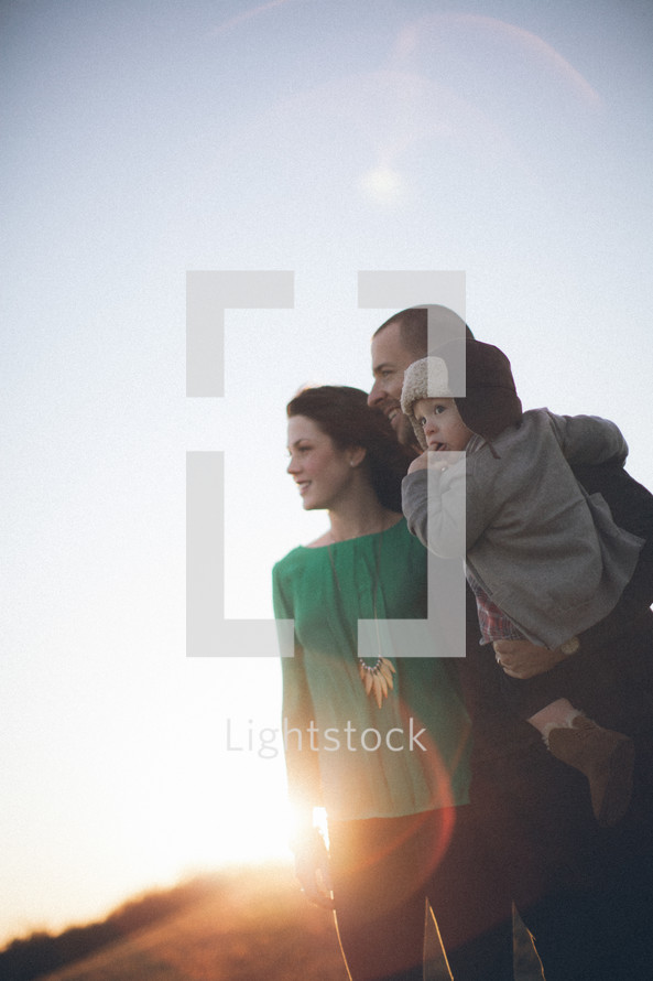 Man holding toddler child standing with woman on grassy hill at sunrise.