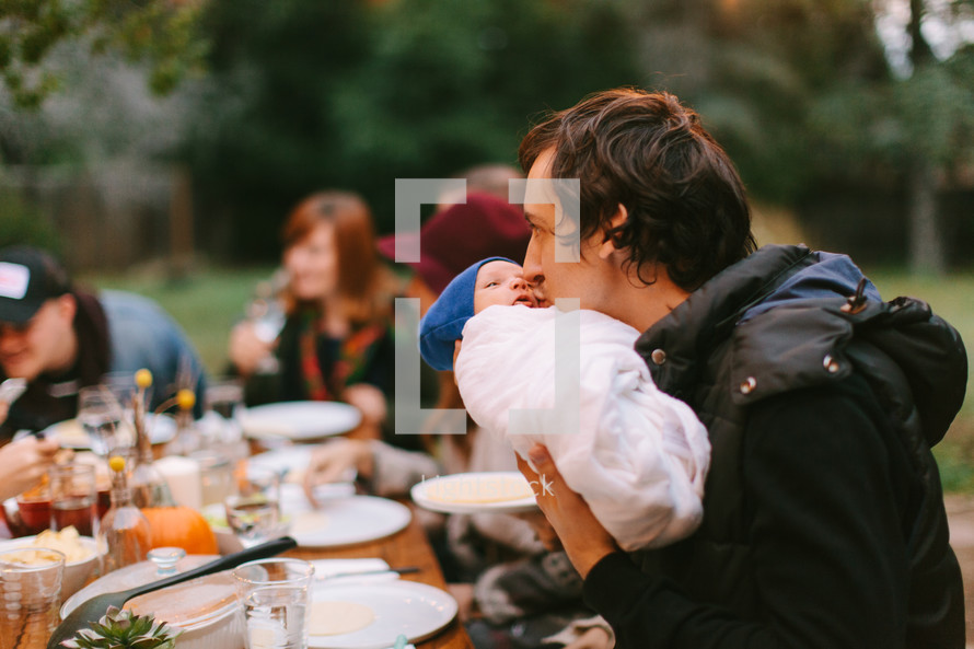 father kissing a baby at a fall dinner party outdoors