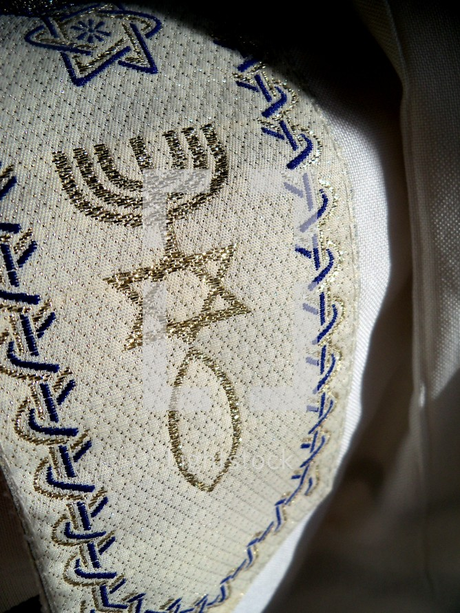 The Hebrew Prayer shawl otherwise known as a Tallit meaning cloak or sheet with Hebrew symbols such as the star of David and the menorah knit in navy blue and gold fabric colors on a white fabric.