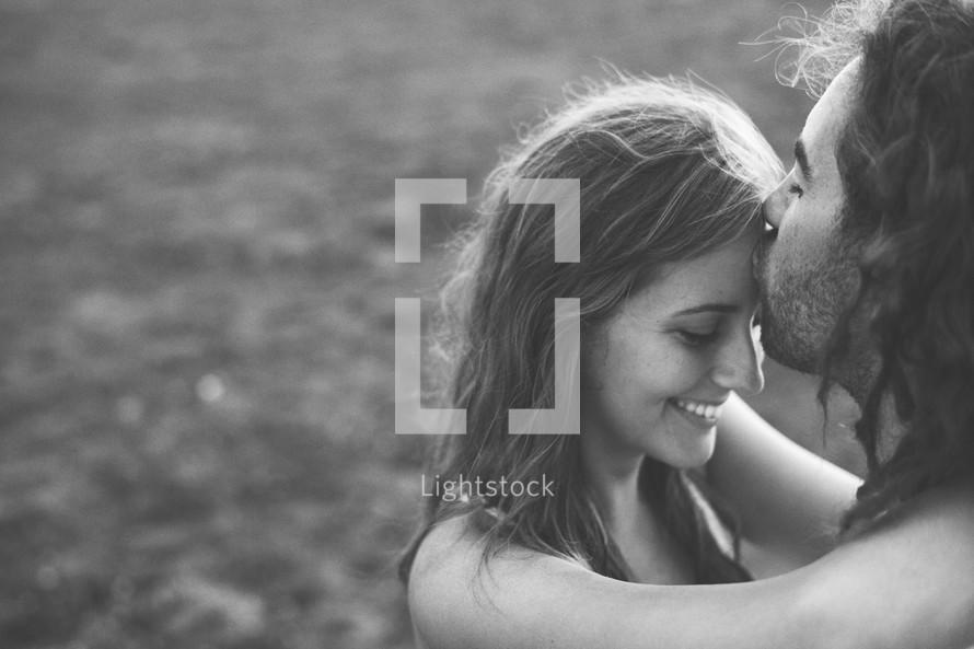 a man plants a tender kiss on a woman's forehead