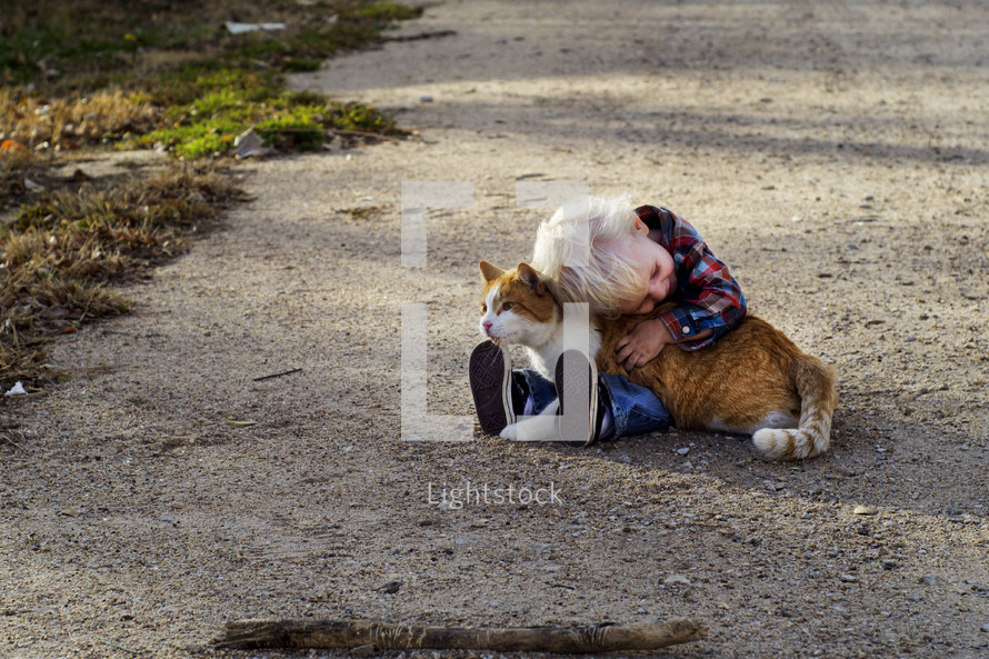 toddler boy hugging a cat