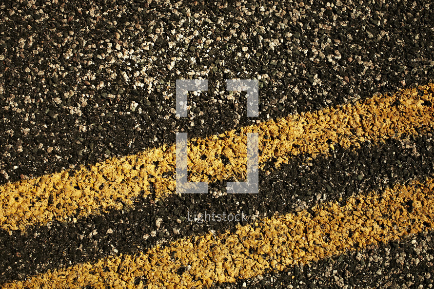 A closeup of a double yellow dividing line painted on a road.