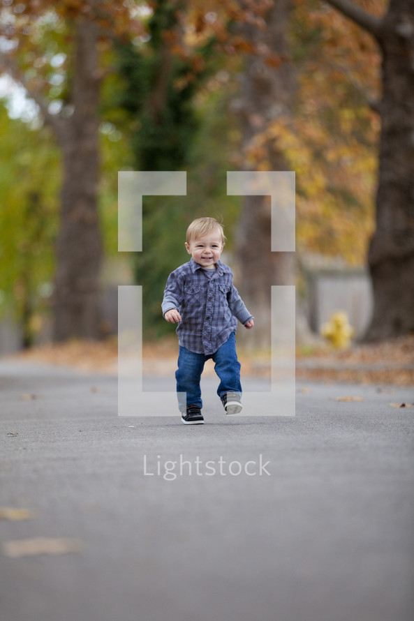 Toddler boy walking outside