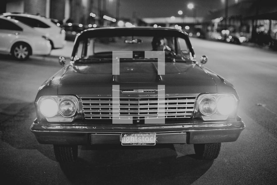 A vintage car shines its headlights