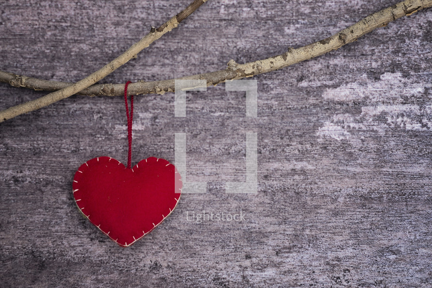 a felt heart ornament hanging on a branch