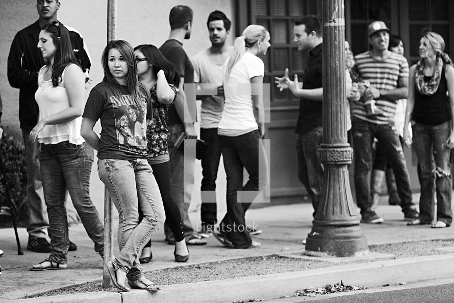 A group of young people socializing on the sidewalk girl alone on street outreach ministry young adults