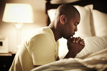 An African American man bowing in prayer before bedtime.