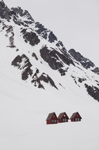 red lodges at the bottom of snow covered mountain peaks