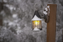 A snow covered lantern on a wooden post.
