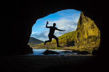 silhouette of a man leaping in the entrance of a cave