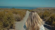 woman walking on a path towards a beach