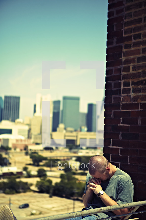A white, young adult man praying on top of a building