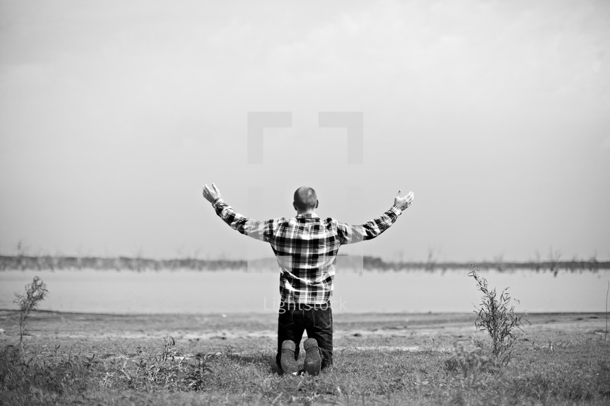 Man on his knees - arms raised - worshipping