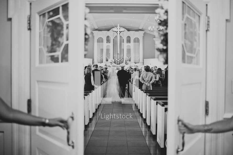 A bride and her father walking down an aisle