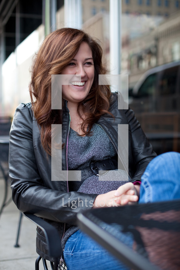 smiling woman sitting at an outdoor table
