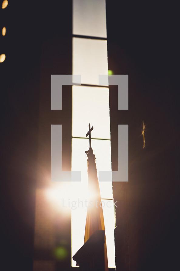 sun shining through a church window onto a cross