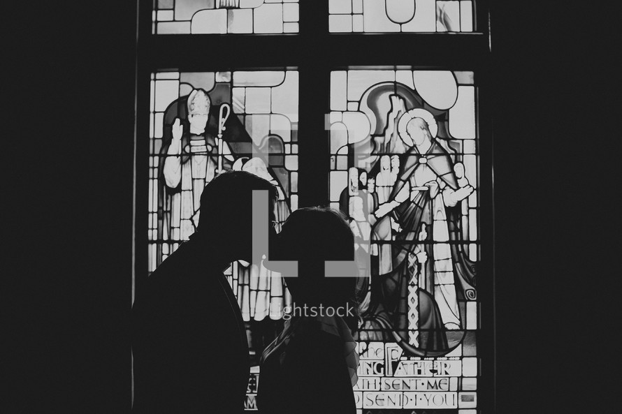 A silhouetted couple kissing in front of a stained glass window