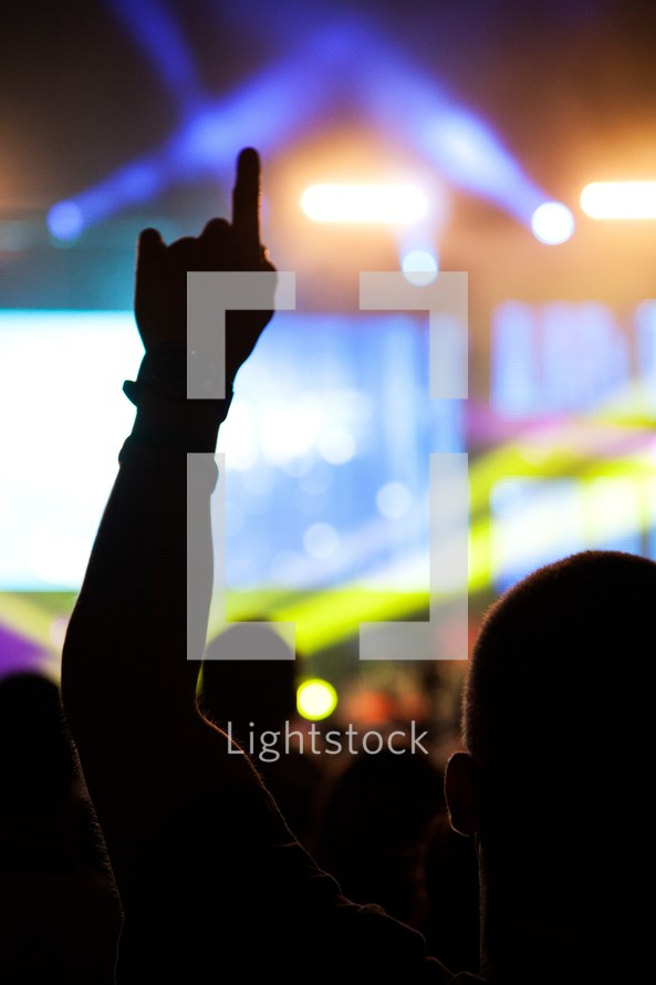 Silhouette of man watching concert on lighted stage with left hand pointer finger raised in the air.