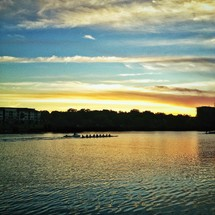 Rowing team on lake at sunset.