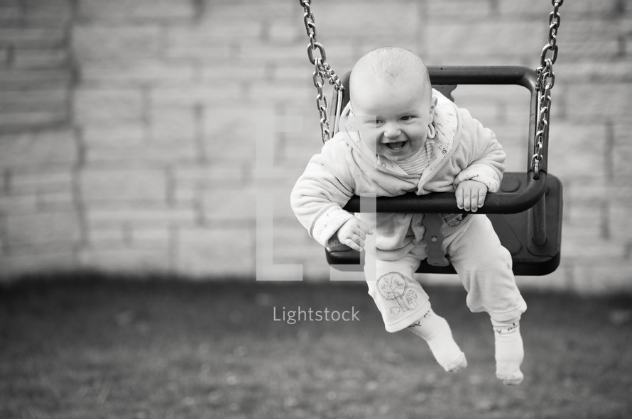 a happy baby swinging on a swing