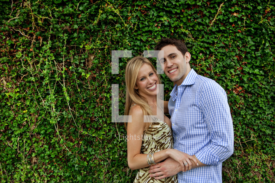 a couple hugging in front of an ivy covered wall