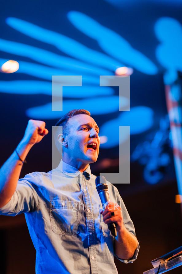 Man pastor preacher speaking into microphone, declaration, encouragement pulpit