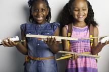 girls holding school supplies