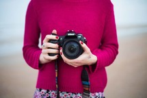 a woman photographer holding a camera