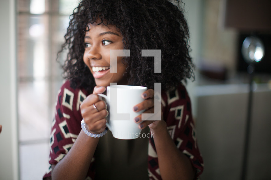 A smiling young woman holding a coffee mug.