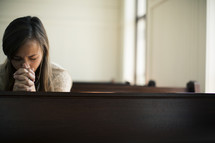Woman praying in a church pew.