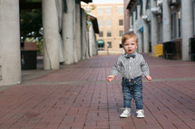 toddler boy in a bow tie standing on a sidewalk