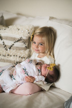 big sister holding a newborn baby
