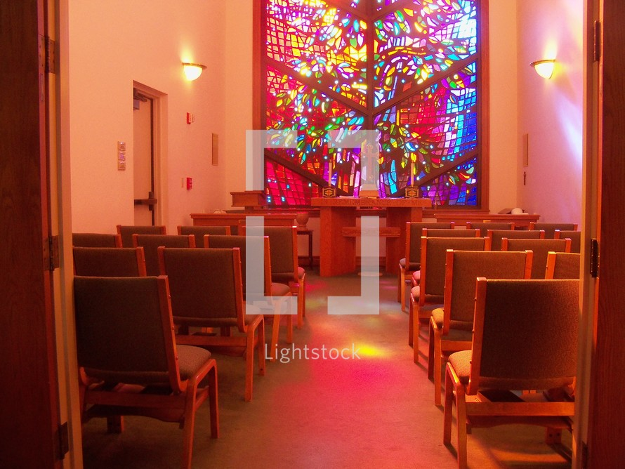 A colorful stained glass window lights up a prayer chapel with warm color and light to reflect peace, warmth, light and love.
