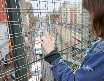 a woman looking through a wire cage at traffic below