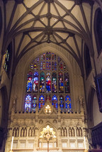 stained glass windows above an altar