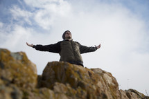 man standing on a mountainside with raised arms