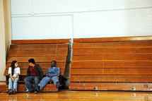 teens sitting on bleachers in a gymnasium