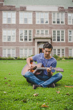 young man sitting in grass playing a guitar