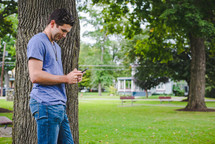 man standing beside a tree texting