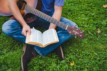 young man sitting in grass playing a guitar and reading a Bible