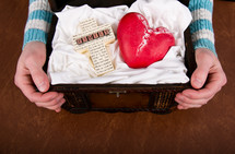 Hands holding a treasure chest containing a family cross and a red ceramic heart.